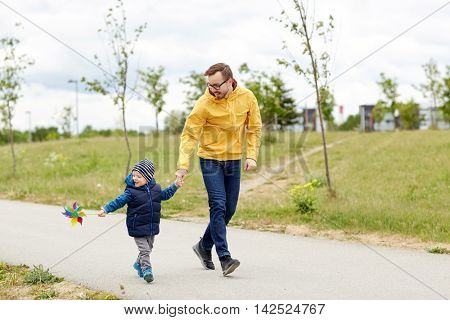 family, childhood, fatherhood, leisure and people concept - happy father and little son with pinwheel toy walking outdoors