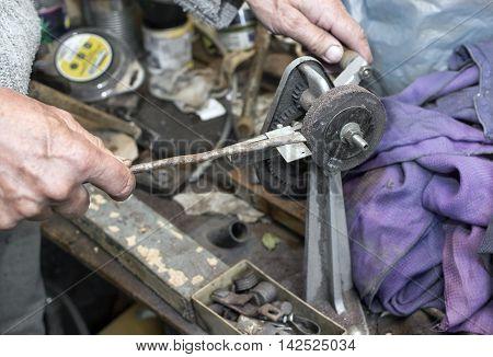 Hands of mechanic working on a retro grindstone closeup indoor shot