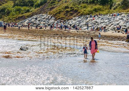 ROBIN HOODS BAY ENGLAND - AUGUST 12: A mother holding her little boy's hand in the sea. In Robin Hoods Bay North Yorkshire England. On 12th August 2016.
