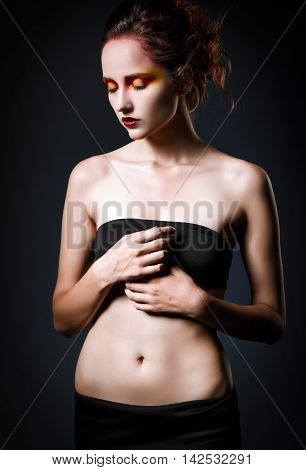 Dramatic studio portrait of a beautiful sad redhead girl