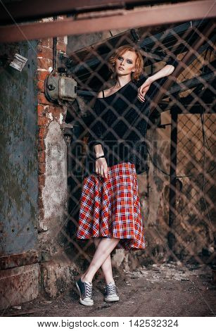 Portrait of a beautiful grunge girl in plaid skirt and sweater standing behind metallic lattice