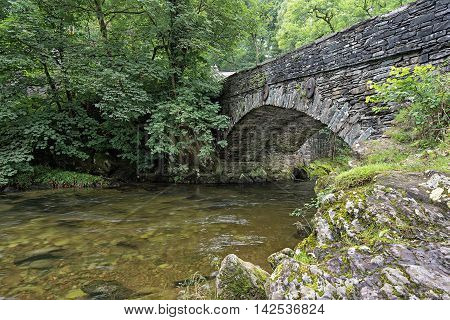 Great Langdale beck flows under Elterwater bridge. Elterwater is a popular walking meeting point for walkers and tourists exploring Great Langdale in the Lake District National Park, Cumbria, England.