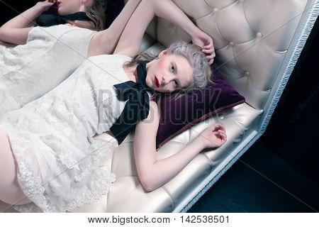 Blonde girl lying on the sofa in the boudoir Modern interpretation of Marie Antoinette