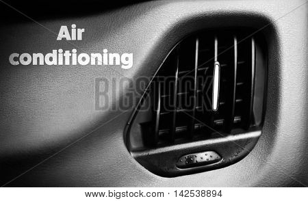 Car air vent with text air conditioning on dashboard. Air conditioning concept.