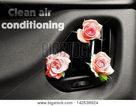 Roses in car air vent with text clean air conditioning on dashboard. Air conditioning concept.