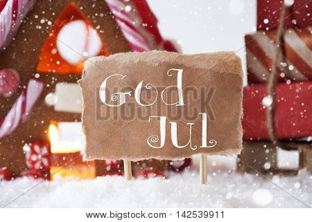 Gingerbread House In Snowy Scenery As Christmas Decoration. Sleigh With Christmas Gifts Or Presents And Snowflakes. Label With Swedish Text God Jul Means Merry Christmas