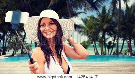 lifestyle, leisure, summer, technology and people concept - smiling young woman in sun hat taking picture with smartphone on selfie stick over tropical beach with palms and swimming pool background