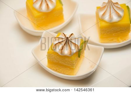 Mini lemon meringue cake with cream top on plate shot on a white background