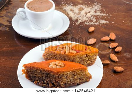Baklava cup of black coffee and almonds on table in café or old coffee table