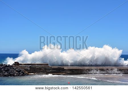 A big wave crashing on a seawall