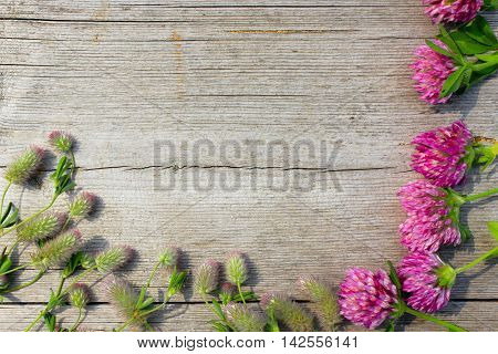 decorative ikebana with flowers of clover and meadow flowers on the wooden surface