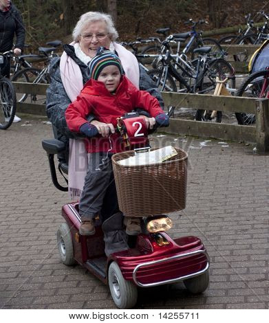 elderly lady riding on a mobility scooter with child