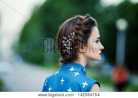 Young fashion woman with a crystal hairpin in hair on city background