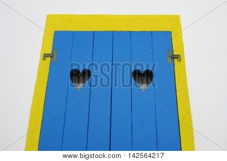 yellow window frame and blue wooden door with two hollow heart shape gaps of a house front in Moinhos village at Sao Miguel Azores island in Portugal in conceptual love and welcome concept