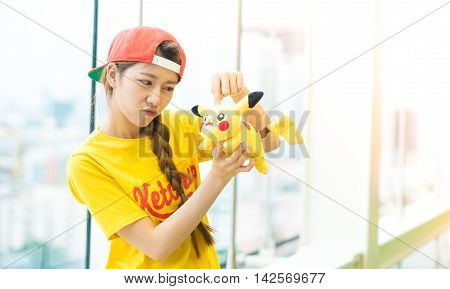 BANGKOK THAILAND – August 142016: Trainer girl playing pokemon pokemon ball Lighting with sun flare