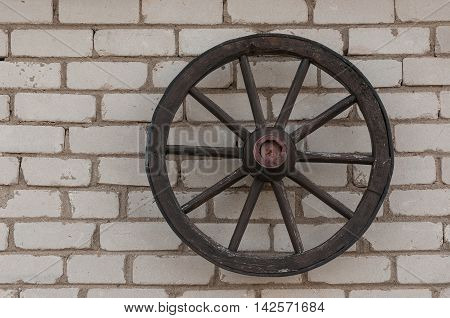 Horse carriage wheel on the old brick wall. Cartwheel.