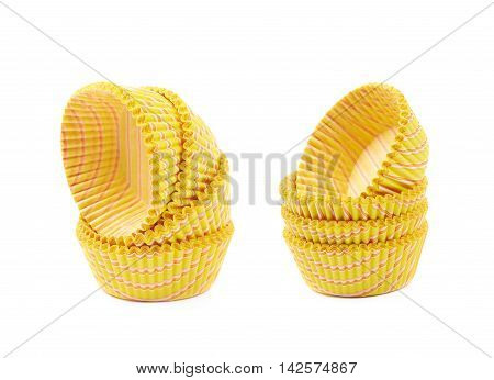 Pile of multiple yellow paper cupcake cups, composition isolated over the white background, set of two different foreshortenings