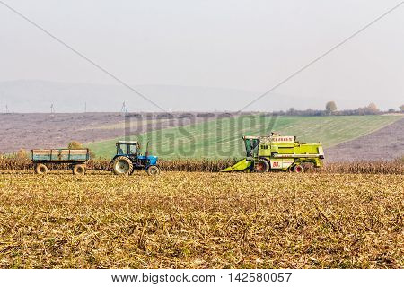 Tractor And Harvester In Autumn Field