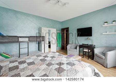 Spacious bedroom with a double and a two-tier beds. Interior design