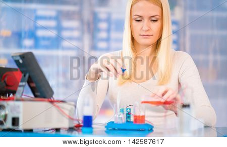 Woman scientist with hydrogen fuel cell in laboratory
