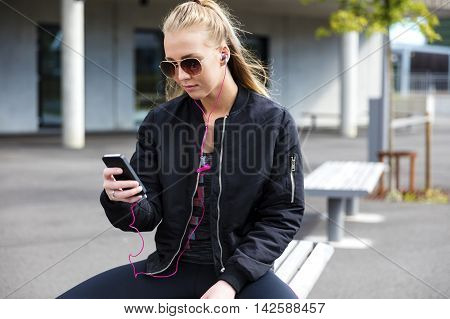 Beautiful woman with sunglasses sits on a bench in the city wearing a jacket and sportswear. Listens to music and using smart phone.