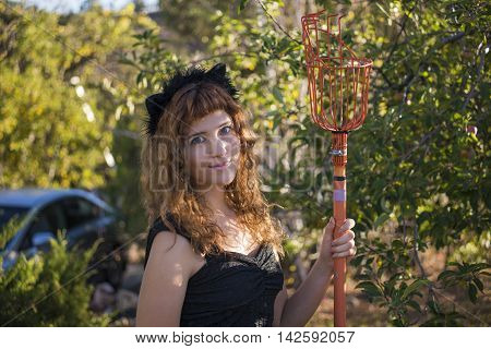 Young woman as cat on Halloween apple picking with fruit clipper picker stick and red hair