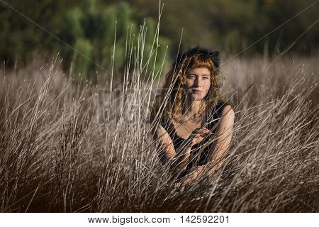 Young female in tall dry hay grass in black dress and red hair