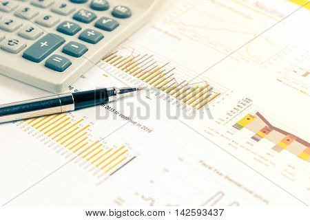 Close up of pen on financial documents with calculator in background. Business concept photo with sunlight filter.
