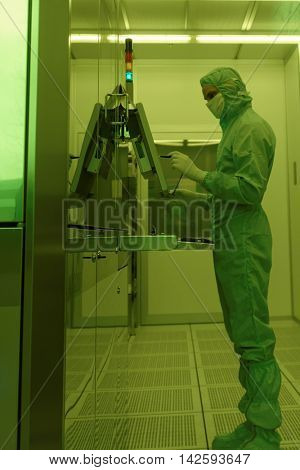 ST. PETERSBURG, RUSSIA - APRIL 18, 2016: Man in cleanroom suite working in clean room at JSC