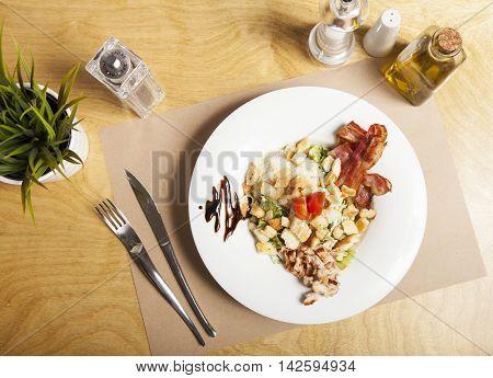 Portion of fresh cesar salad. Roast chicken fillet and vegetables