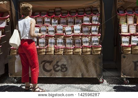 Granada Spain - August 5 2016: tourist buying spices seeds and tea sold in a traditional street market