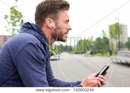 Middle Age Active Male Sitting And Listening To Music