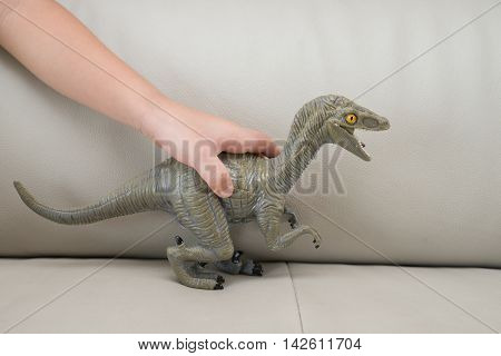 kids hand catching a greu Deinonychus toy on a sofa at home