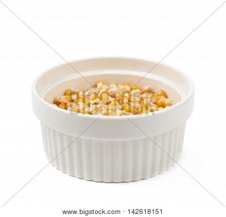 White ramekin dish filled with multiple corn kernels isolated over the white background