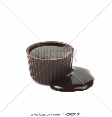 Chocolate confection candy spilled with the liquid cocoa syrup isolated over the white background