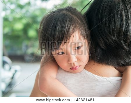 Asian baby girl hugging her mother sleepy
