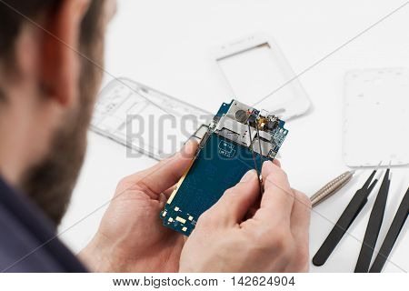 Repairman disassembling smartphone with tweezers. Unrecognizable male repairer holding mobile phone circuit in electronics repair service, white background poster