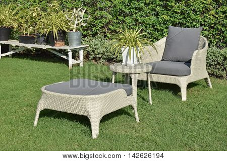 green garden with an outdoor furniture lounge group with rattan chairs sofa and table