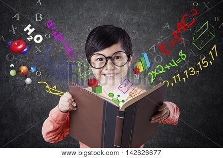 Cute little girl standing in the classroom while reading a book with formula of math science and physics