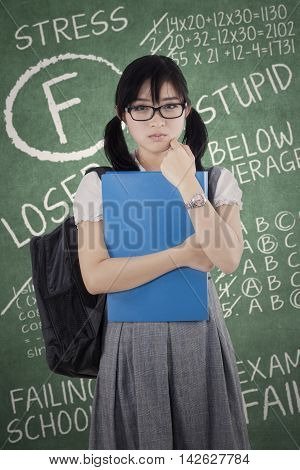 Sad college student standing in the classroom with failed exam score on the blackboard