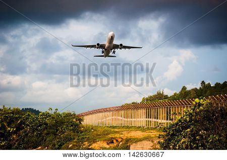 the plane is take off to sky from airport and over plant tree and fence among warm light