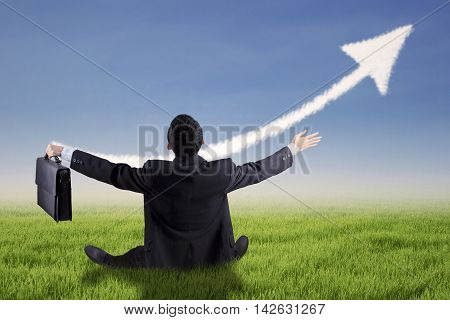 Back view of successful businessman sitting on the meadow while holding a briefcase with upward arrow on the sky