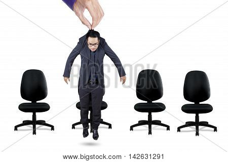 Young businessman hanging on a hand above office chairs in the studio isolated on white background