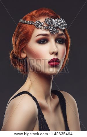 Beautiful young woman with smoky eyes and full red lips. Massive crystal hair accessory on head. Studio beauty shot. Copy space.