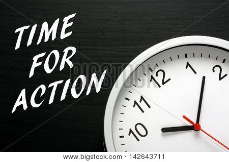 The words Time For Action written in white text on a blackboard next to a modern wall clock