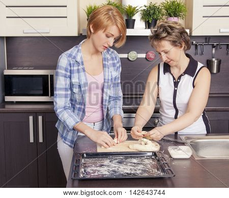 Mom and daughter preparing cookies in the kitchen at home