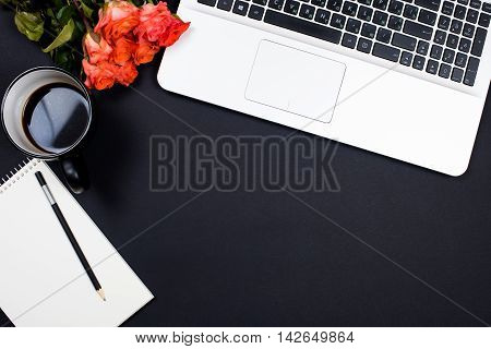 Businessman desk workspace with laptop keyboard, coffee and notepad on black background. Startup concept, top view mockup.