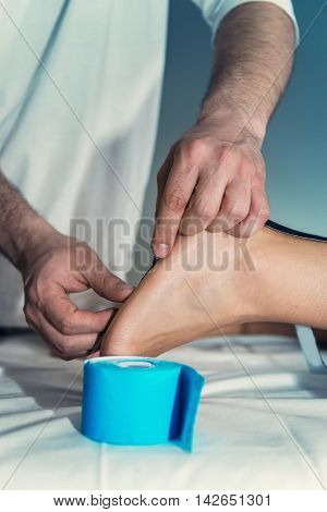 Therapist applying kinesio tape to patient's foot