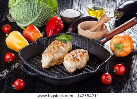 Tasty Grilled chicken fillet and bell pepper on a pap on the black wooden table.