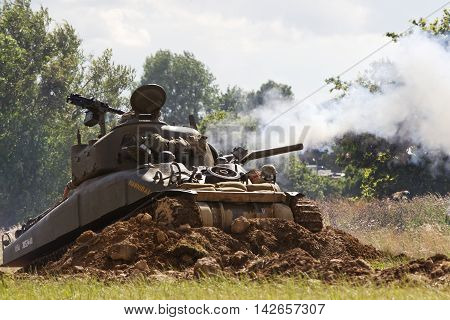 WESTERNHANGER, UK - JULY 25: Reenactors fire simulated tank shells towards the German lines during a WW2 battle re-enactment scenario at the War & Peace show on July 25, 2015 in Westernhanger
